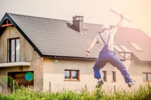 a builder jumping with joy in front of the house