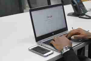 hands on a laptop next to a phone, looking through Google